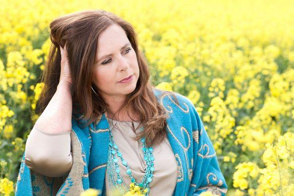 Egy sárga virágú repcemezőn közép korú nő ül, vállán türkizkék kendő, a fejét támasztja a jobb kezével.