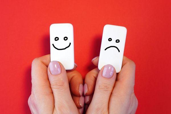 Egy piros háttér előtt egy női kéz, egyikben kis fehér kártya mosolygós, a másikban szomorú ikonnal.