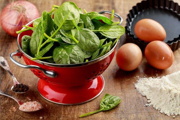 Egy asztalon tojások, hagyma, kanalakban só és bors, liszt, mellette egy piros tésztaszűrőben spenót.