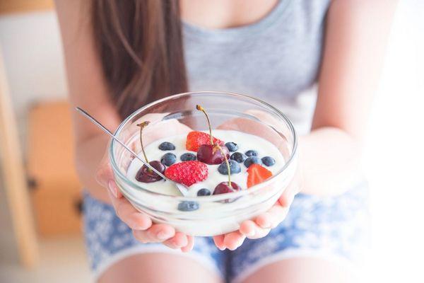 Egy fiatal lány ül a széken, kezében egy tál, melyben probiotikus joghurt gyümölcsökkel, eperrel, fekete áfonyával, cseresznyével.
