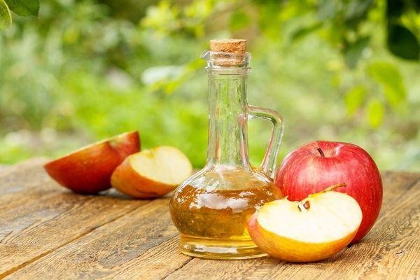 Egy asztalon egész és félbevágott almák, mellettük üvegkancsóban almaecet.