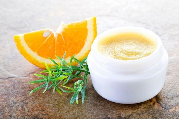 Egy asztalon narancsszelet, rozmaringág és fehér tégelyben C-vitaminos gyulladáscsökkentő bőrtápláló krém.