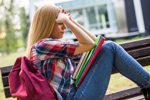 Egyetemista lány egy padon fáradtan ülve a fájós fejét fogja.
