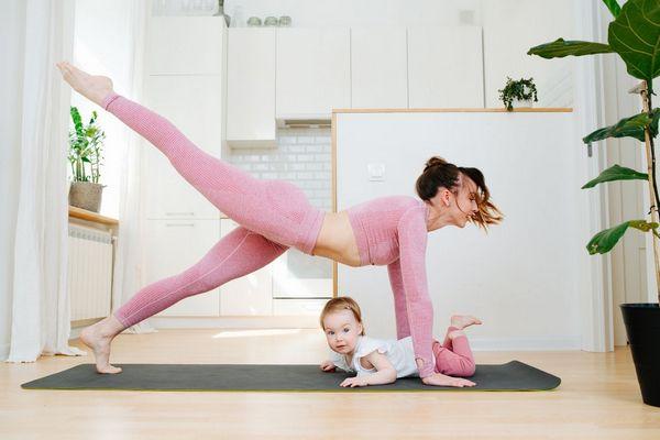 Egy fiatal anyuka rózsaszínű sportruhában kislányával otthon fájós hátát tornáztatja.