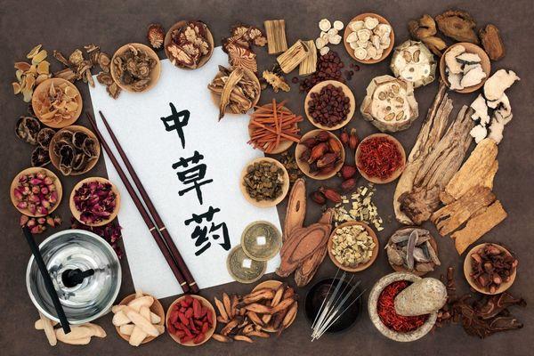 Egy asztalon kis tálakban kínai orvoslás alapjaiként szolgáló gyógynövények, gombák, magvak, mellettük evőpálcikák, fűszermozsár és kínai írásjeleket tartalmazó papír.