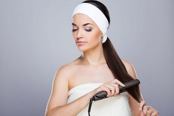 Egy szürke háttér előtt fiatal hölgy áll, fején törölköző, hosszú barna haját sütővassal egyenesíti.