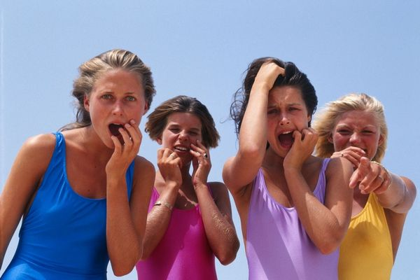 Négy fiatal nő fürdőruhában a kamerába nézve viccesen ijedt arcot vág.