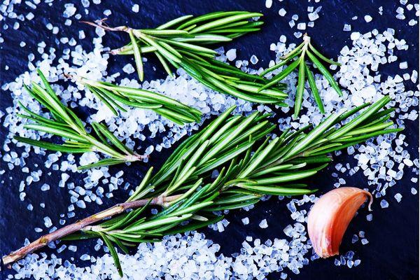 Kék háttér előtt só szétszórva, mellette rozmaringágak és fokhagymagerezd.