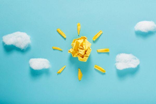Egy kék háttér előtt vattából készült felhők között sárga papírból formázott nap.