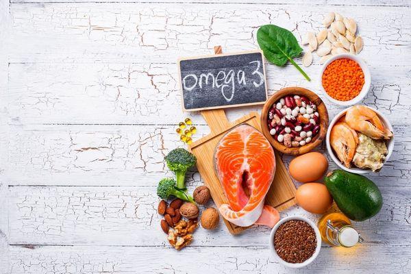Egy asztalon omega-3 zsírsavat tartalmazó élelmiszerek, lazac, brokkoli, dió, mandula, avokádó, tojások, lenmag és bab tálakban, rák, lencse, tökmag, spenótlevél, halolajkapszulák.