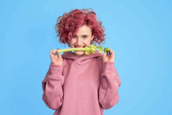 Kék háttér előtt egy vörös hajú lány szárzellert tart a fogaival, miközben mosolyog.