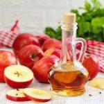 Egy asztalon piros kockás terítő és saláta előtt egész és felszeletelt almák, mellettük egy üvegkancsóban almaecet.