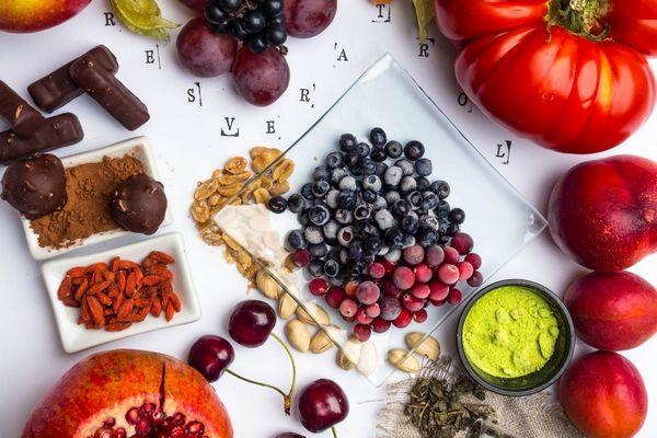 Egy asztalon resveratrolt tartalmazó élelmiszerek, paradicsom, barack, fekete és vörös áfonya, szőlő, cseresznye, gránátalma, gojibogyók, étcsokoládé, mellettük resveratrol felirat. .