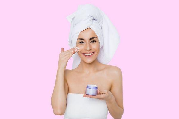 Egy fiatal lány rózsaszínű háttér előtt ekcémás arckrémmel az arcát keni, kezében egy arckrémes tégely.