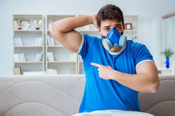 Egy kék pólós férfi otthon gázálarcban az izzadt hónaljára mutat.