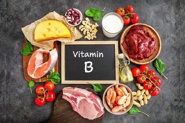 Egy asztalon tábla B-vitamin felirattal, körülötte B-vitaminokat tartalmazó élelmiszerek, sajt, lazac, paradicsom, vörös hús, spenót, rák, földimogyoró, máj, tej, kesudió, tarkabab.