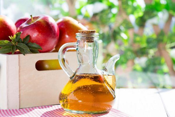 Egy piros kockás terítőn egy ládában almák, mellette üvegben almaecet.