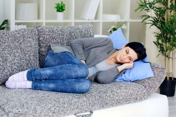Egy szürke kanapén fiatal nő az oldalán fekszik felhúzott lábakkal, kezével a fájós hasát fogja.