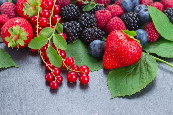 Egy asztalon bogyós gyümölcsök, eper, piros ribizli, szeder, fekete áfonya, málna.