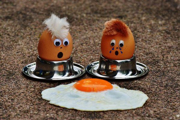 Egy asztalon két tojás tojástartóban, szemek és szájak ragasztva rájuk, mellettük egy tükörtojás, amit siratva néznek.