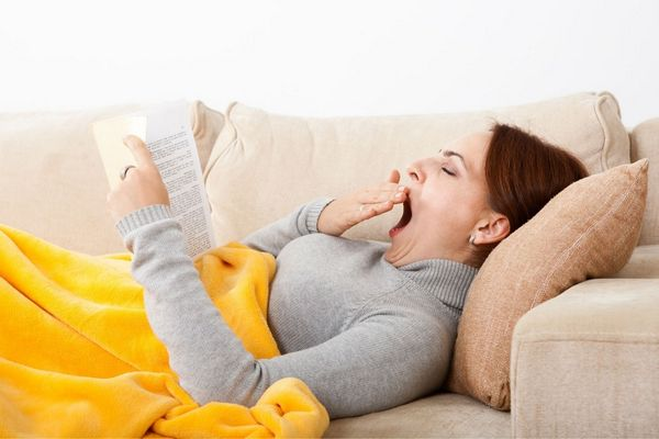 Egy fiatal nő a kanapén fekszik, sárga takaróval betakarózva könyvet olvas, közben ásít.