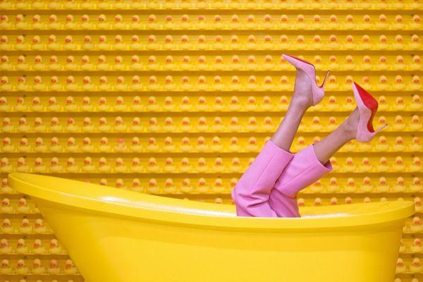 Egy sárga háttér előtt sárga fürdőkádban fekszik egy nő rózsaszínű nadrágban és cipőben.
