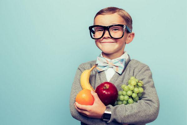 Egy iskolás kisfiú nagy fekete keretes szemüvegben mosolyogva áll, kezében alma, narancs, banán és egy fürt szőlő.