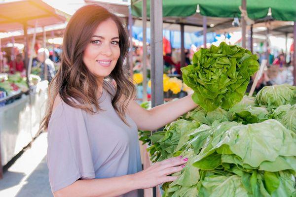 Egy fiatal nő a piacon zöldséges pultnál áll, salátát tart a kezében.
