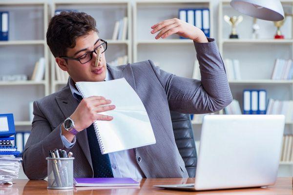 Fiatal öltönyös férfi az irodában az íróasztalnál ül, karját felemeli, orrán csipesz, hogy az izzadságszagát ne érezze.