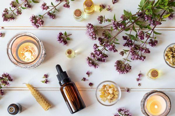 Egy asztalon oregánóvirágok, mellette egy barna üvegcsében oregánóolaj és mécsesek.