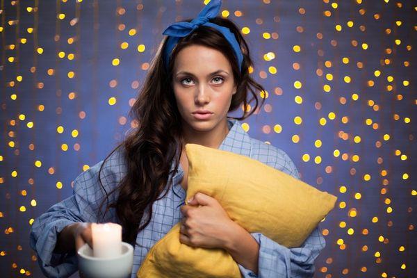 Egy lila háttér előtt fiatal nő álmatlanul áll pizsamában, kezében egy sárga párna és egy gyertya.