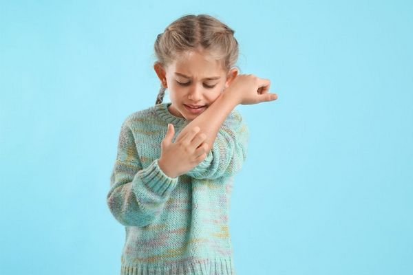 Egy világoskék háttér előtt egy kislány vakarja a viszkető karját.