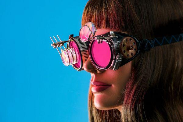 Egy kék háttér előtt egy fiatal nő szemvizsgáló szemüveget visel, melyre sok lencse van feltéve.