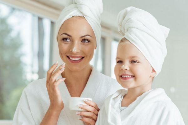 Egy fürdőszobában anya és kislánya fehér köntösben, fejükön fehér törölköző, arckrémmel kenik az arcukat.