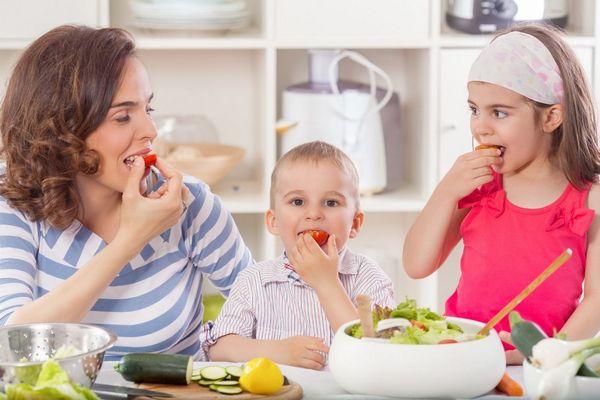 Egy konyhában anya és két gyermeke, kisfia és kislánya zöldségeket eszik, paradicsomot, uborkát, salátát,
