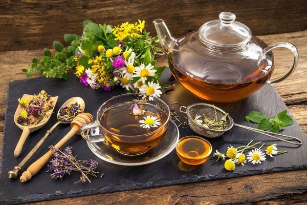 Egy asztalon üveg teáskannában és üveg teáscsészében gyógytea, mellettük kis tálban méz és szárított gyógynövények és gyógynövényekből készült virágcsokor.