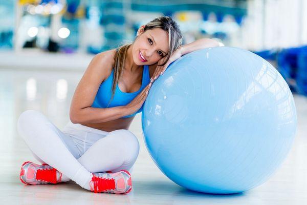 Egy fiatal nő sportruhában egy kék színű fitneszlabdára hajolva mosolyog.