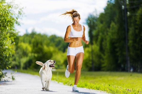 Fiatal lány sport ruhában a kutyájával együtt fut egy erdei úton.