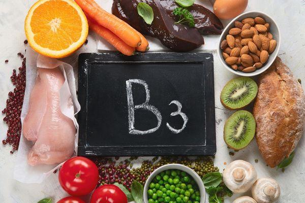Egy asztalon B3-vitamint tartalmazó élelmiszerek, narancs, sárgarépa, máj, tojás, mandula egy tálban, kivi, teljes kiőrlésű kenyér, gomba, borsó, lencse, spenót, paradicsom, csirkehús.