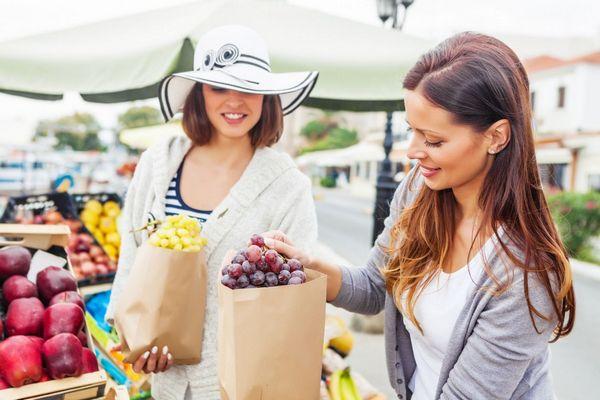 Két fiatal nő a piacon biogyümölcsöket vásárol, szőlőt tesznek papírzacskóba.
