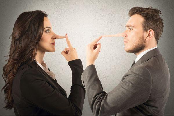 Egy szürke háttér előtt egy nő és egy férfi egymással szemben állva az orrukra mutatnak, amely megnyúlt, mint a Pinokkió orra, jelezve a hzugságot.