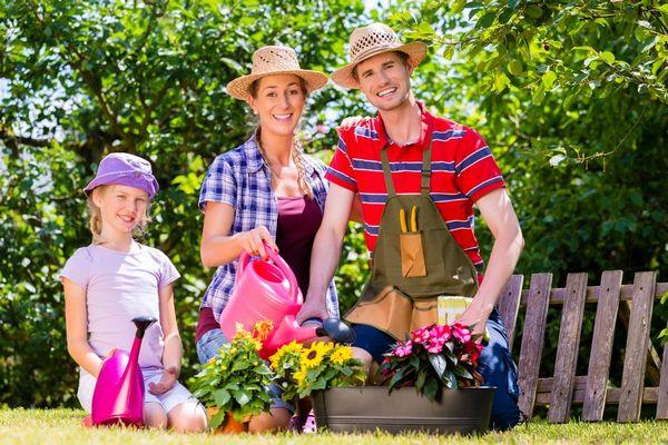 Egy család, anyag, apa és kislányuk a kertjükben virágokat locsolnak.