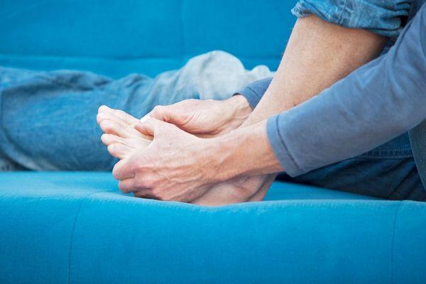 Egy kék kanapén ülő nő két kezével a köszvényes fájós talpát fogja.