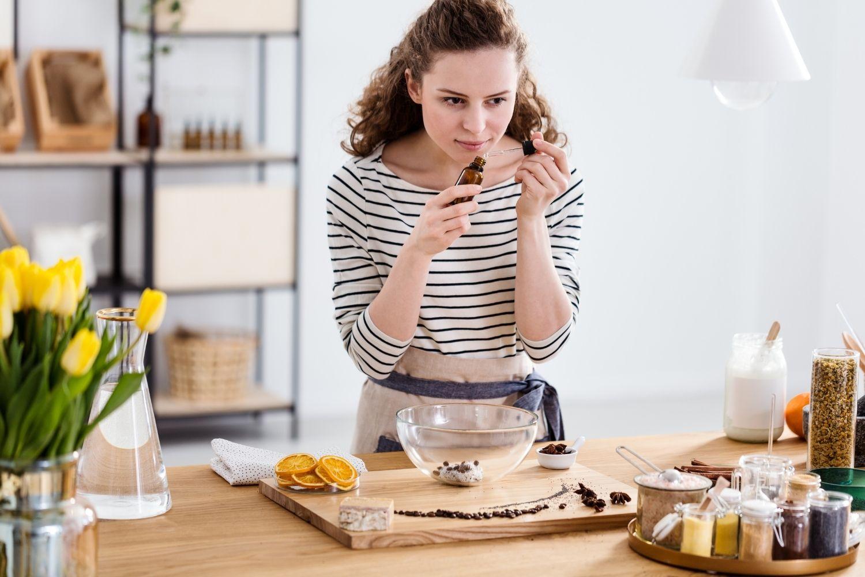 Otthon, a konyhában fiatal lány illóolajokat szagolgat, natúr kozmetikumot készít.