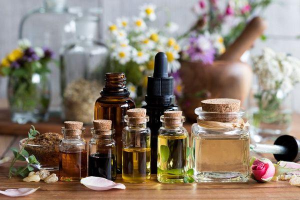 Egy asztalon több üvegcse, melyekben különböző illóolajok vannak, mellettük gyógynövények,