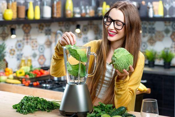Egy fiatal lány a konyhájában zöld leveles zöldségeket rak a turmixgépébe, káposztát, uborkát, salátát, és fűszernövényeket.
