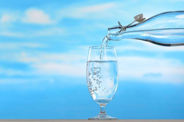 Kék háttér előtt egy üvegpohárba ivóvizet töltenek egy vizespalackból.
