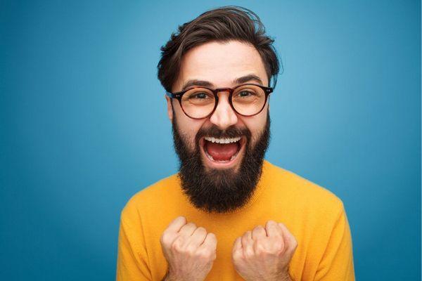 Kék háttér előtt sárga pólós szakállas, szemüveges férfi nevet.