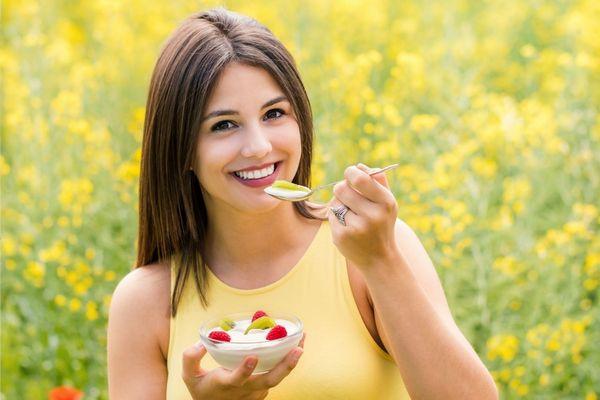 Fiatal hölgy virágos mezőn sárga pólóban gyümölcsös joghurtot eszik.