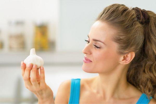 Egy fiatal nő jobb kezében egy fokhagymát tart.